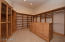 Her closet offers a variety of storage options including glass doors, velvet lined jewelry drawers, hamper, retractable valet bars, and more. Loads of overhead storage space and windows providing natural light!