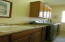 Granite counter top with utility sink, and cabinets for storage. Washer and Dryer