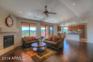 Great room with open floor plan, new wood flooring, gas fireplace, views, custom valances & sliding door to balcony