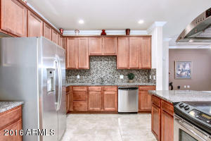Large Chef's Gourmet Kitchen with walk-in pantry, granite countertops, tiled backsplash, upgraded cabinets, stainless steel appliance package