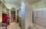 Large walk-in master closet with custom cabinetry