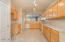 Kitchen features tile floors, lots of counter space and cabinetry for storage.