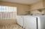 With a full wall of shelving opposite the washer and dryer that are included in the sale