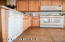 White appliances accent the light wood in the cabinets