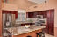 Remodeled kitchen with stainless steel appliances, dark brown cabinetry, brand new granite, glass mosaic backsplash, LED lighting mounted under cabinets.