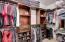 Custom walk-in closet with his and her organizer drawers, shelfs and racks.