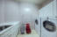 The spare laundry room has built-in cabinets and a sink. Washer and dryer DO NOT convey.