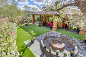 Backyard is perfect for entertaining with a built-in fire pit and benches, a fountain, and a large covered patio