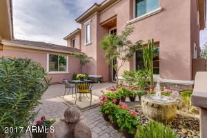 Privately gated front Courtyard lavishly landscaped with colorful flora, serene bubbling water feature, & paver stones.