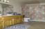Honey oak cabinets, tile flooring, tub/shower.