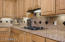 Kitchen offers gas cooktop with granite back splash with custom accent pieces.