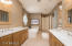 Separate vanities in the master bathroom with jetted tub and walk in shower.