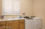 Laundry features a sink and cabinetry for storage.