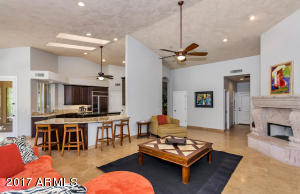 Soaring Ceilings, Travertine Floors, Cantera Stone Fireplace, Lots of Windows and opens to Chefs Kitchen!
