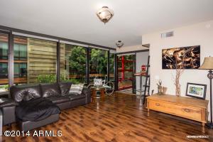 Living room with wood flooring & floor to ceiling windows.