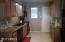 large kitchen has newer cabinets, granite countertops, tile backsplash and black appliances.