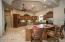 Kitchen features two islands, stainless steel appliances, ample lighting, wine refrigerator, under counter lighting, travertine back splash and walk in pantry