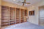 VIEW OF AMPLE CUSTOM SHELVING IN DEN/OFFICE PLUS DOOR TO A WALK-IN CLOSET WITH SHELVING!