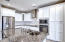 Stainless steel appliances, granite counters and white linen painted cabinets.