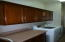 LAUNDRY ROOM. MAPLE CABINETS WITH CHERRY FINISH, CROWN MOLDING WITH ROPE INLAY. LAMINATE COUNTER SPACE