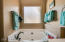 Master bathroom features dual sinks, separate tub and shower, neutral paint, and a HUGE walk-in closet