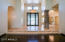 Foyer with Cantera Stone Pillar and Trim, Travertine Flooring and Intricate Glass Door.