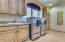 Spacious Laundry Room with Custom Cabinetry, Sink, Folding Station, Ironing Board and Desk Area.