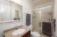 Your master bath has an extra-large vanity mirror for maximum storage and a step-in shower with glass doors.
