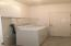 Large laundry room with cabinets and shelves
