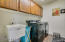 Full size laundry room with built in cabinets and sink.