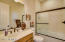 Sizable guest bathroom with obscure glass enclosure.