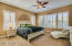 Large master bedroom with beautiful shutters and upgraded carpet.