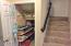 """As you move past the kitchen area on your right you will find this """"hidden"""" pantry with shelves making good use of the space under the stairs."""