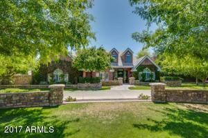 Circular drive and abundant landscaping frame this brick beauty in Gilbert Arizona