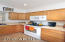 Efficient kitchen with electric range/oven and built in microwave.