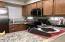 Bright and open kitchen with granite counters and stainless steel appliances.