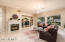 Warm and spacious family room featuring a fireplace and updated lighting.