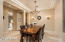 Formal dining room featuring crystal lights chandelier and sconces by Currey & Company.