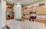 Looking across the large kitchen island at the corner pantry, fridge, oven, and microwave.