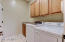 Laundry room includes overhead cabinets and a sink and connects the garage to the house.