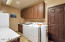 Laundry room with ample cabinet space and sink for added convenience.