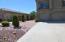 Pavers and plants line walkway to backyard.