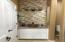 Bathroom #3 features custom ledger stone and tile-work