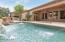 Pool with water features and covered patio.