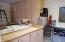 Floor to ceiling cabinets, counter top, built-in desk and sink in single garage