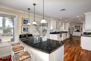 Beautifully appointed kitchen with custom white cabinetry and black granite counters.