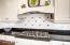 5 burner gas cooktop with custom backsplash. Crisp white subway tile highlights the area.