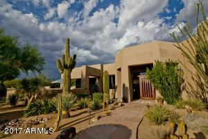 Meandering walkway through professionally landscaped front yard to the front door. Mature saguaros!
