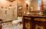 Frameless Shower Doors with rubbed bronze handles. Travertine Shower and custom lighting.