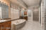 Master bathroom is spacious with a large stone walk-in shower, separate tub, dual vanities with make up vanity, cherry cabinetry, and granite counters.